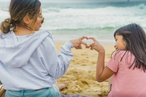 Mother and daughter connecting by seaside